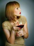 muchacha en una alineada del oro con un vidrio de vino rojo Fotos de archivo
