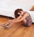 Muchacha en una alineada y las sandalias, sentándose en el suelo Fotografía de archivo libre de regalías