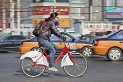 Muchacha en una bici de alquiler en tráfico ocupado, Pekín, China Fotografía de archivo