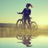 Muchacha en una bicicleta Foto de archivo libre de regalías