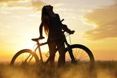 Muchacha en una bicicleta en la puesta del sol Fotografía de archivo libre de regalías
