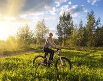 Muchacha en una bicicleta en la puesta del sol imágenes de archivo libres de regalías
