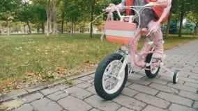 Muchacha en una bicicleta rosada en parque metrajes