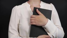 Muchacha en una blusa blanca que hojea a través del libro negro almacen de metraje de vídeo