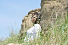 Muchacha en una blusa blanca y vidrios al lado de la roca Fotos de archivo libres de regalías