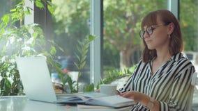 Muchacha en una blusa rayada blanco y negro con un ordenador portátil en sitio brillante almacen de metraje de vídeo