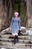 Muchacha en una boina rosada y una capa gris-azul que vienen abajo las escaleras de la casa vieja Imagen de archivo