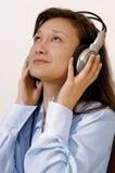 Muchacha en una camisa azul con los auriculares Imagen de archivo libre de regalías