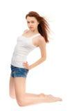Muchacha en una camisa blanca y pantalones cortos azules Fotos de archivo libres de regalías