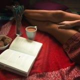 Muchacha en una camisa roja en una tela escocesa que lee un libro sobre una taza de café imagenes de archivo