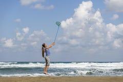 Muchacha en una camiseta adentro rayada en las nubes de las capturas del mar foto de archivo libre de regalías