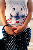 Muchacha en una camiseta blanca con un conejo y una falda azul manchada Foto de archivo libre de regalías