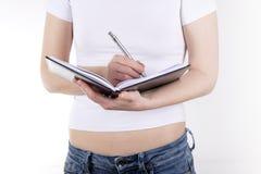 Muchacha en una camiseta blanca con un cuaderno y una pluma Imagen de archivo libre de regalías
