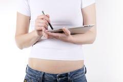 Muchacha en una camiseta blanca con una tableta y una aguja Fotos de archivo libres de regalías