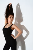 Muchacha en una camiseta negra que presenta en el estudio en un fondo blanco soporte del pelo en extremo Imagen de archivo