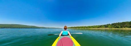 Muchacha en una canoa que flota rio abajo Foto de archivo libre de regalías