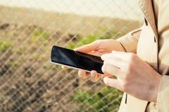 Muchacha en una capa beige que camina abajo de la calle y del teléfono móvil de las aplicaciones Fotos de archivo libres de regalías