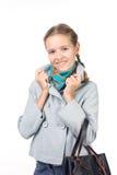 Muchacha en una capa con un bolso Fotografía de archivo libre de regalías