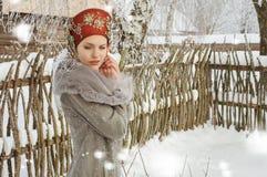 Muchacha en una capa gris y un sombrero retro en invierno fotografía de archivo