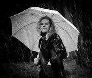 Muchacha en una capa negra y un paraguas blanco que camina abajo de la calle en mismo nevadas fuertes Fotografía de archivo