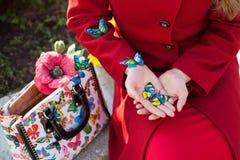 Muchacha en una capa roja a sostenerse en mariposas de las manos imagen de archivo