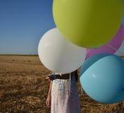 Muchacha en una cara de ocultación del campo detrás de los globos Imagenes de archivo