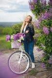 Muchacha en una chaqueta de cuero cerca de la bicicleta blanca Fotografía de archivo