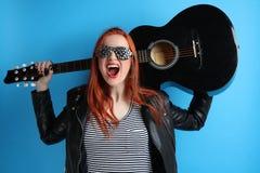Muchacha en una chaqueta de cuero negra con una guitarra Fotografía de archivo