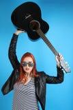 Muchacha en una chaqueta de cuero negra con una guitarra Foto de archivo libre de regalías