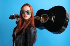 Muchacha en una chaqueta de cuero negra con una guitarra Imagenes de archivo