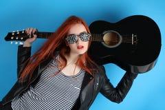 Muchacha en una chaqueta de cuero negra con una guitarra Fotos de archivo