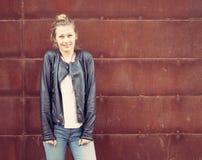 Muchacha en una chaqueta de cuero negra que presenta en una pared oxidada del metal outdoor Fotografía de archivo