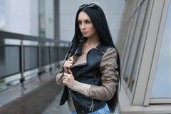 Muchacha en una chaqueta de cuero que se coloca cerca del edificio Imagen de archivo libre de regalías