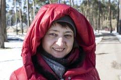 Muchacha en una chaqueta roja al aire libre en invierno en el parque Fotos de archivo