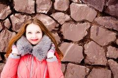 Muchacha en una chaqueta roja sobre una pared de ladrillo Imagen de archivo libre de regalías