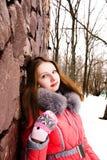 Muchacha en una chaqueta roja sobre una pared de ladrillo Fotografía de archivo libre de regalías