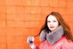 Muchacha en una chaqueta roja sobre una pared de ladrillo Foto de archivo libre de regalías