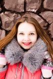 Muchacha en una chaqueta roja sobre una pared de ladrillo Foto de archivo