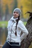 Muchacha en una chaqueta y un sombrero contra un árbol con las hojas de otoño Fotos de archivo libres de regalías