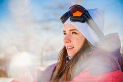 Muchacha en una chaqueta y vidrios de esquí en un día de primavera soleado en el MES imágenes de archivo libres de regalías