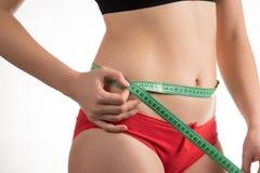 Muchacha en una cintura de la dieta y un centímetro y miradas de medición del abdomen Imagenes de archivo