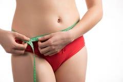 Muchacha en una cintura de la dieta y un centímetro y miradas de medición del abdomen Imágenes de archivo libres de regalías