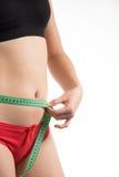 Muchacha en una cintura de la dieta y un centímetro y miradas de medición del abdomen Fotografía de archivo libre de regalías
