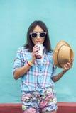 Muchacha en una ciudad con el casquillo en el batido de leche de consumición de la camisa, jugo fresco, gozando, morenita, maquil Fotografía de archivo