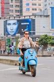 Muchacha en una e-bici con la cartelera en el fondo, Kunming, China Fotos de archivo
