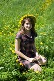 Muchacha en una guirnalda contra un prado Fotos de archivo