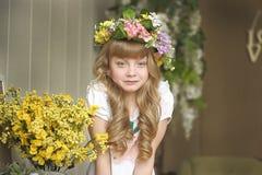 Muchacha en una guirnalda de flores Imágenes de archivo libres de regalías