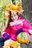 Muchacha en una guirnalda de hojas de arce con la calabaza Imagenes de archivo