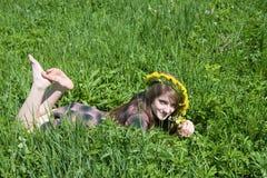 Muchacha en una guirnalda que miente de prado Fotos de archivo