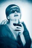 Muchacha en una máscara con un vidrio Imagen de archivo libre de regalías